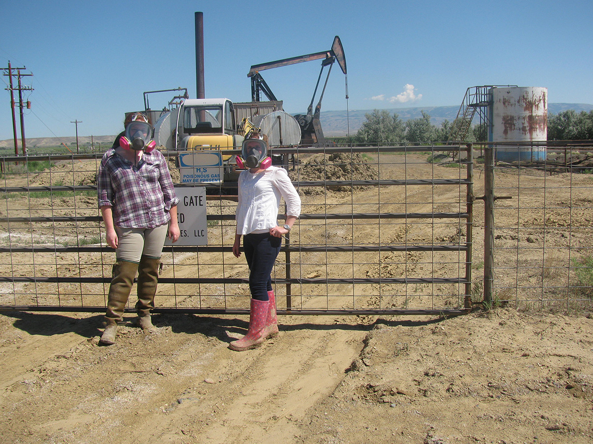 two women wearing gas masks in front of a natural gas operation
